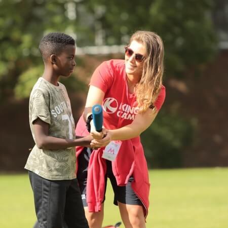 a red top helping a child with a rounders bat