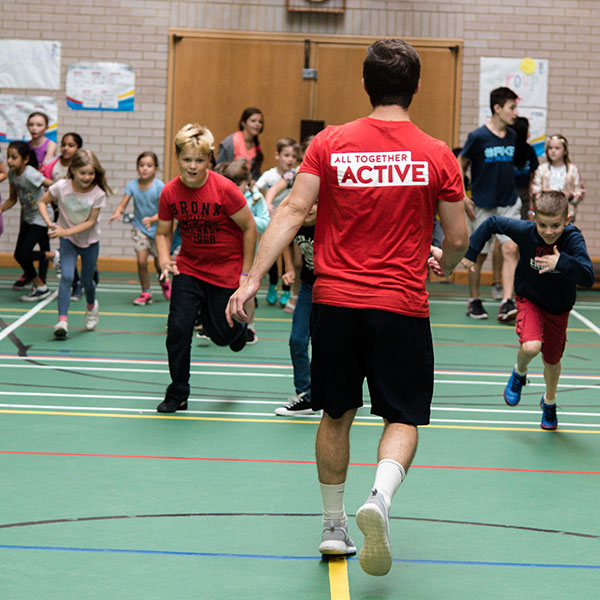 children and a red top running inside a sports hall