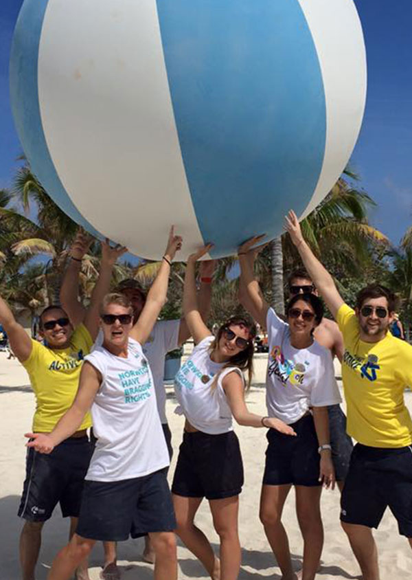 a group of staff on the beach holding a giant beach ball above their head