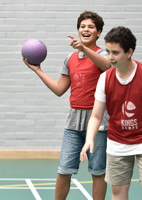 two children stood, one with a sports ball in his hand