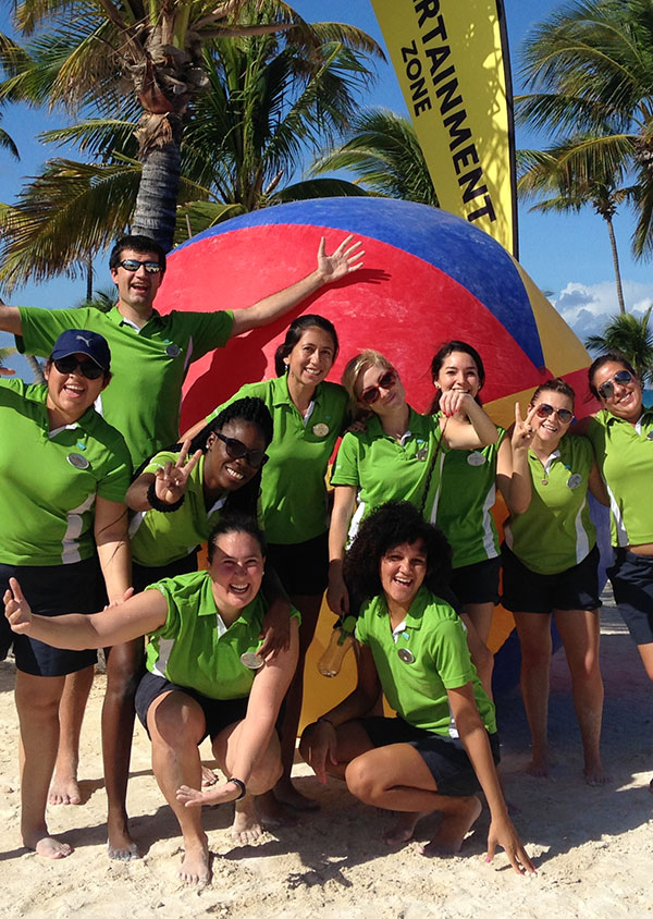 a group of staff membes on the beach smiling and having fun