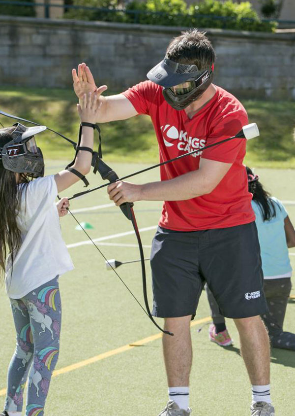 a red top and a child giving each other a high 5 and playing archery tag