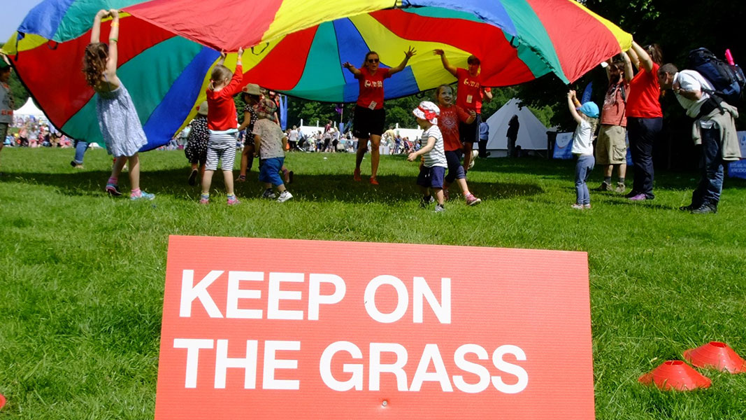 children taking part in parachute games with a sign saying 'keep on the grass' in the forefront