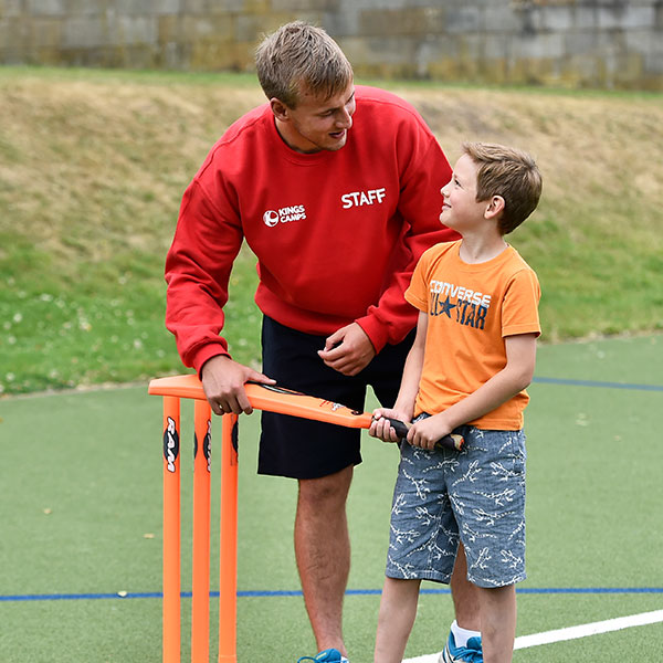 a red top helping a child play ricket