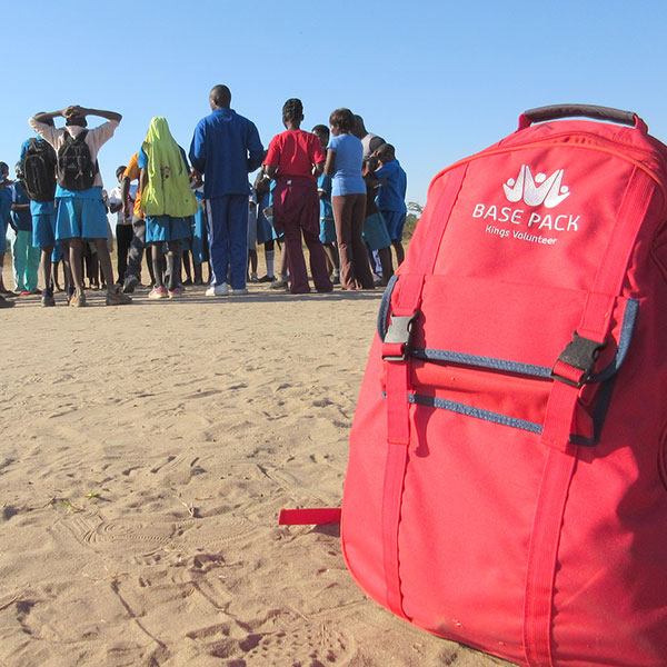 a base pack on the sand with a group of people in the background