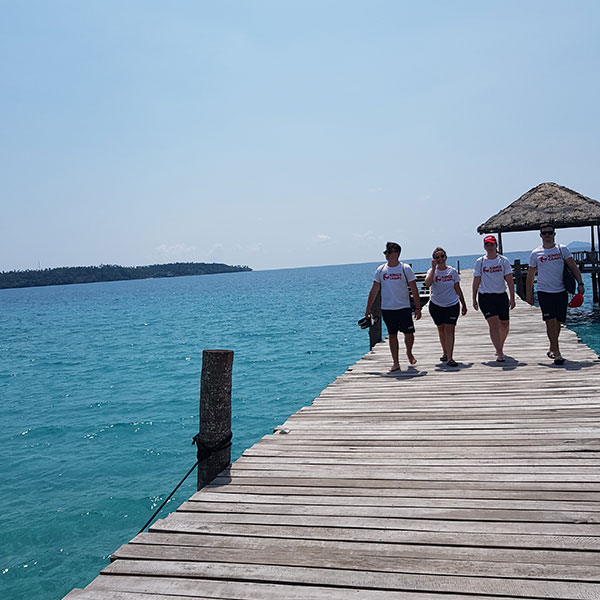 a group of staff walking on a board walk next to the sea