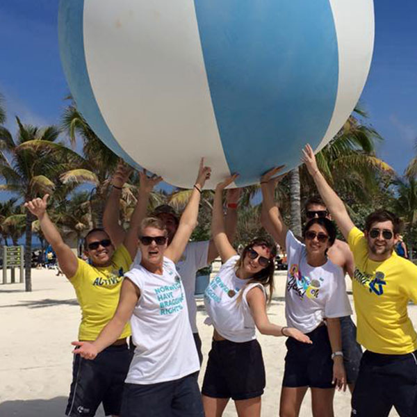 a group of staff members on the beach holding a giant beach ball in the air
