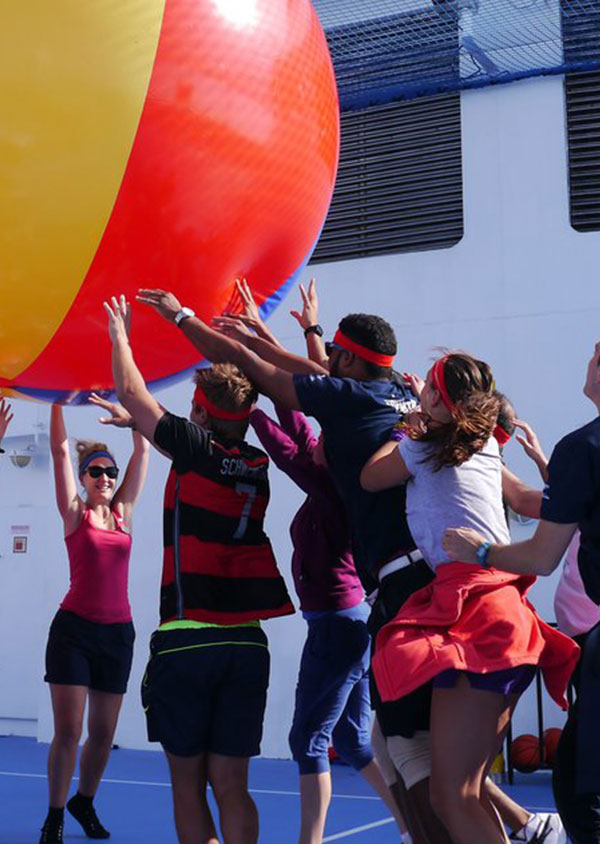 a group of people enjoying activities with a giant beach ball