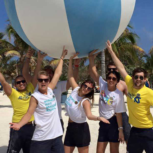 a group of staff on the beach holding a giant beach ball above their head